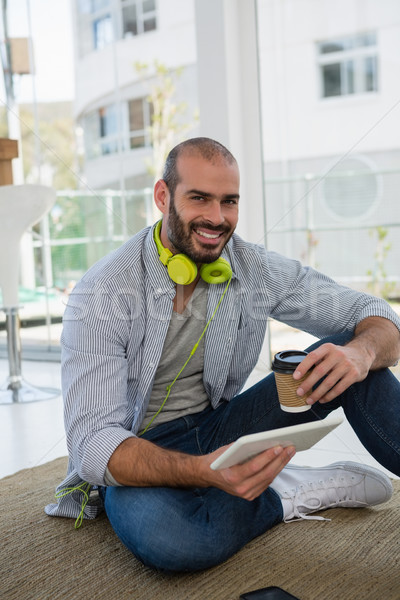 Portrait of designer holding disposable cup and tablet computer while sitting on floor Stock photo © wavebreak_media