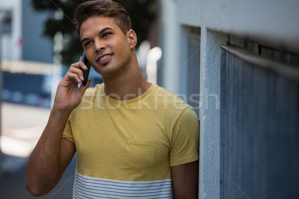 Young man looking away while talking on mobile phone Stock photo © wavebreak_media
