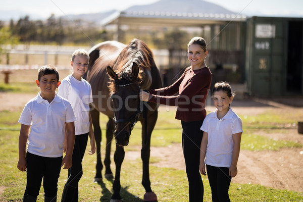 Happy family standing with a brown horse in the ranch Stock photo © wavebreak_media