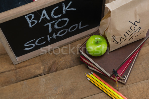 Stock photo: Lunch paper bag, green apple and slate with text back to school on wooden table