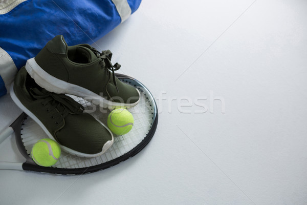 Sports shoe and tennis balls on racket by bag Stock photo © wavebreak_media