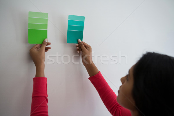 Young woman holding color swatches by wall Stock photo © wavebreak_media