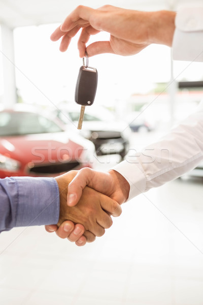 Businessman giving car key while shaking a customer hand Stock photo © wavebreak_media