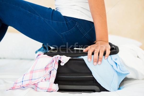 Kobieta posiedzenia walizkę domu bed worek Zdjęcia stock © wavebreak_media