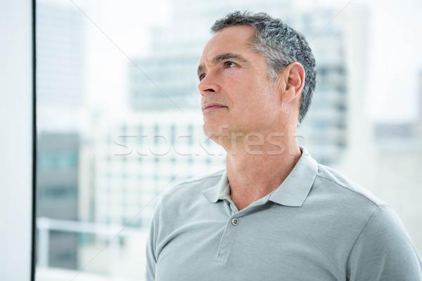 Tensed man standing against window Stock photo © wavebreak_media