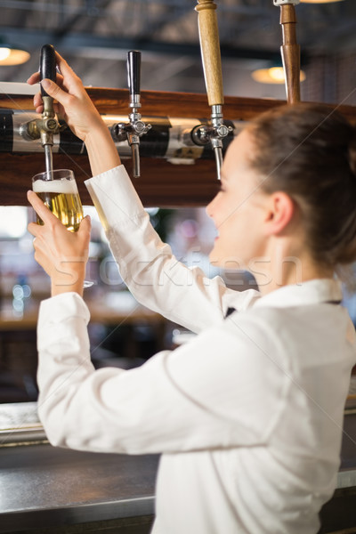 Barmaid pouring beer Stock photo © wavebreak_media