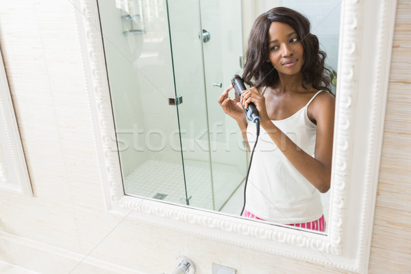 Reflection of young woman straightening hai Stock photo © wavebreak_media