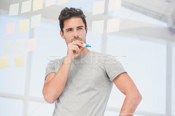 Zamyślony człowiek patrząc karteczki okno biuro Zdjęcia stock © wavebreak_media