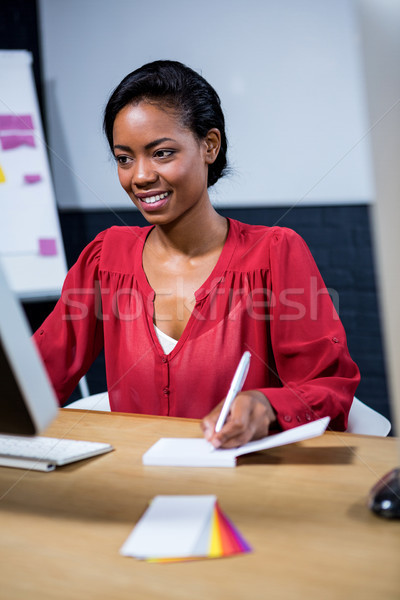 Stock photo: Woman noting on diary while using computer