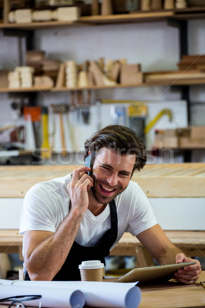 Carpenter calling someone and holding his tablet Stock photo © wavebreak_media
