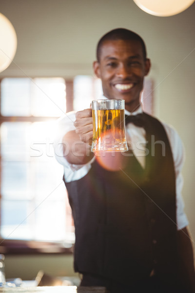Sorridere barista offrendo vetro birra bar Foto d'archivio © wavebreak_media