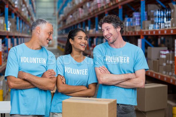 Gelukkig vrijwilligers lachend naar ander armen Stockfoto © wavebreak_media