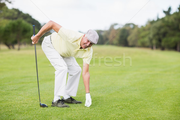 Smiling mature man holding golf club while bending on grassy fie Stock photo © wavebreak_media
