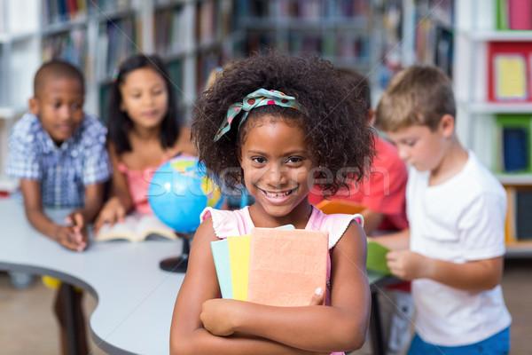 Happy girl holding books against classmates Stock photo © wavebreak_media