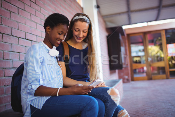 Stock photo: Schoolgirls using mobile phone
