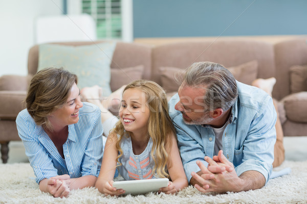 Happy family using digital tablet while lying on floor in living room Stock photo © wavebreak_media