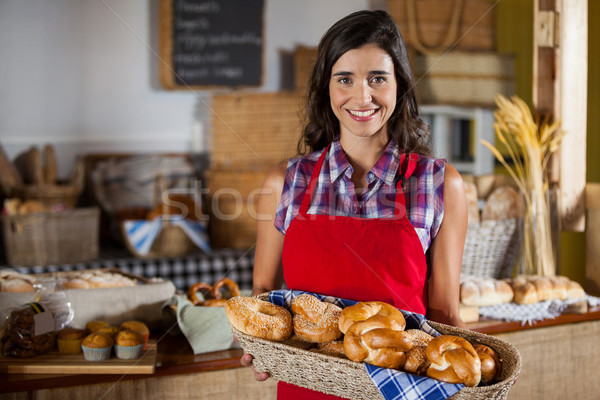 Smiling female staff holding wicker basket of various breads at counter Stock photo © wavebreak_media