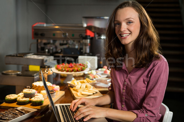 Femme utilisant un ordinateur portable boulangerie contre marché portrait Photo stock © wavebreak_media