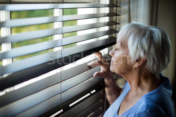 Senior donna guardando fuori finestra cieco Foto d'archivio © wavebreak_media