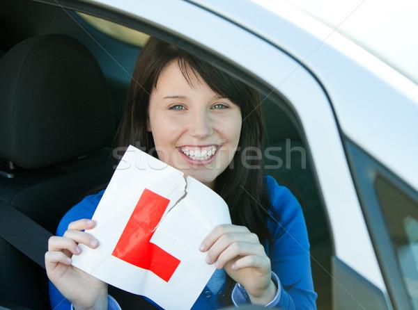 Smiling brunette teen girl sitting in her car tearing a L-sign Stock photo © wavebreak_media