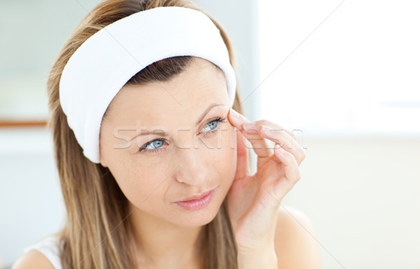 Young woman putting creme on her face wearing a headband in the bathroom Stock photo © wavebreak_media