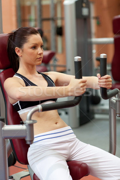 Self-assured athletic woman using a shoulder press in a fitness center Stock photo © wavebreak_media