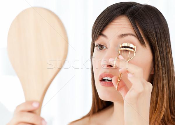 Woman curling her eyelashes Stock photo © wavebreak_media