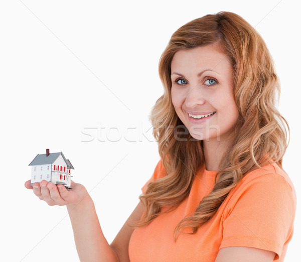 Cute woman holding an house model on a white background Stock photo © wavebreak_media