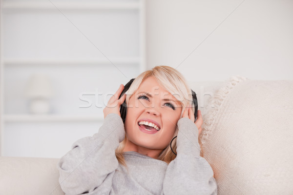 Belo jovem loiro mulher fones de ouvido sofá Foto stock © wavebreak_media
