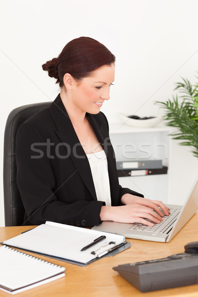 Young beautiful red-haired woman in suit typing on her laptop while sitting in an office Stock photo © wavebreak_media
