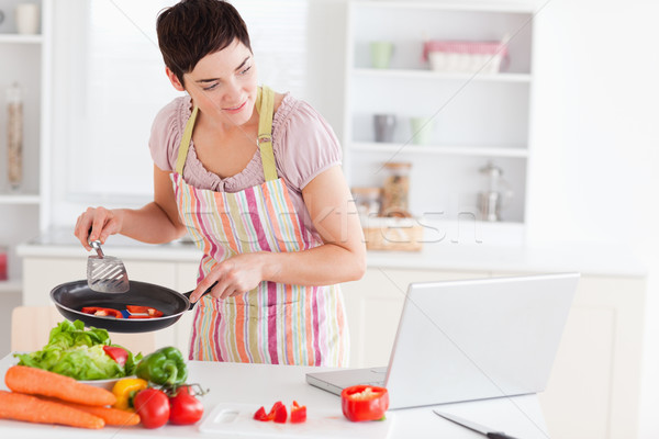 Beautiful woman cooking with receipt on laptop in the kitchen Stock photo © wavebreak_media