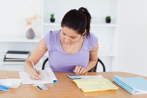 Fiatal nő könyvelés nappali nő papír munka Stock fotó © wavebreak_media