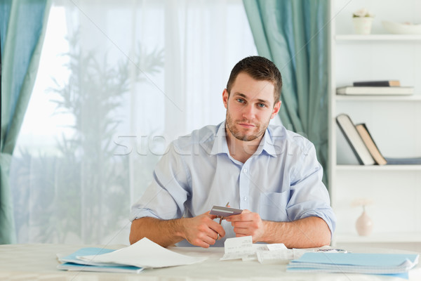 Stock photo: Sad young businessman has to destroy credit caed
