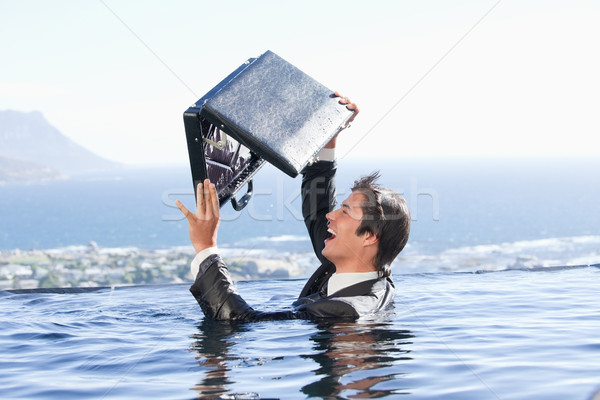 Businessman looking in his briefcase in a swimming pool Stock photo © wavebreak_media