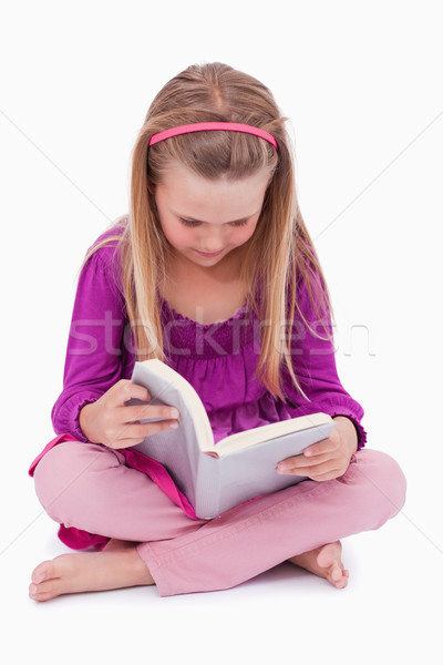 Portrait of a cute girl reading a book against a white background Stock photo © wavebreak_media