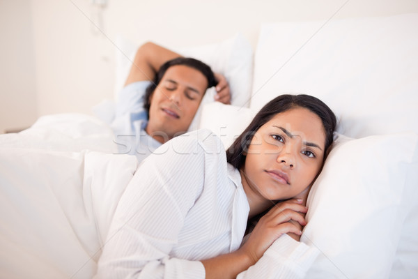 Young woman lying awake next to her sleeping boyfriend Stock photo © wavebreak_media