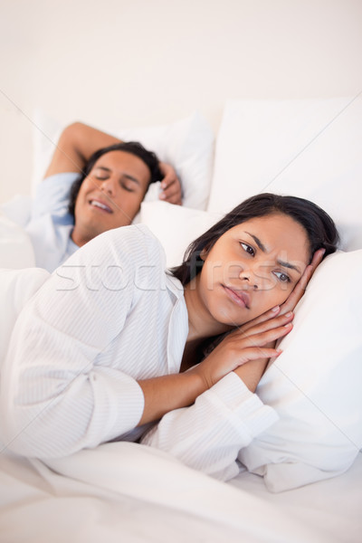 Displeased young woman lying next to snoring boyfriend Stock photo © wavebreak_media