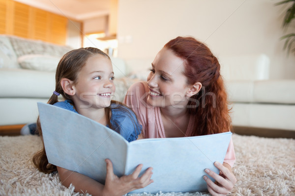 Mother and daughter together with periodical on the floor Stock photo © wavebreak_media