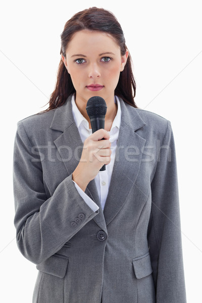 Close-up of a serious businesswoman holding a microphone against white background Stock photo © wavebreak_media