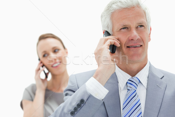 Close-up of a white hair businessman talking on the phone with a smiling woman in background Stock photo © wavebreak_media