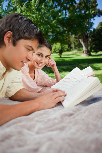Woman looking to the side as she reads a book with her friend while lying prone on a grey blanket in Stock photo © wavebreak_media
