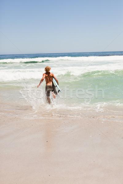 Giovani uomo esecuzione acqua tavola da surf Foto d'archivio © wavebreak_media