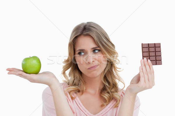 Thoughtful young blonde woman hesitating between a fruit and chocolate Stock photo © wavebreak_media