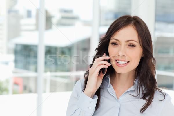 Young smiling manager talking seriously on the cell phone in front of the window Stock photo © wavebreak_media