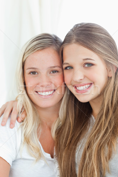 A close up shot of a smiling pair of sisters who are looking at the camera  Stock photo © wavebreak_media