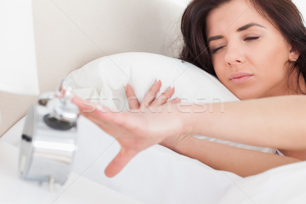 Brunette woman turning off her alarm clock in her bedroom Stock photo © wavebreak_media