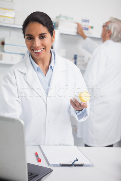 Female pharmacist holding a drug box while smiling in hospital ward Stock photo © wavebreak_media