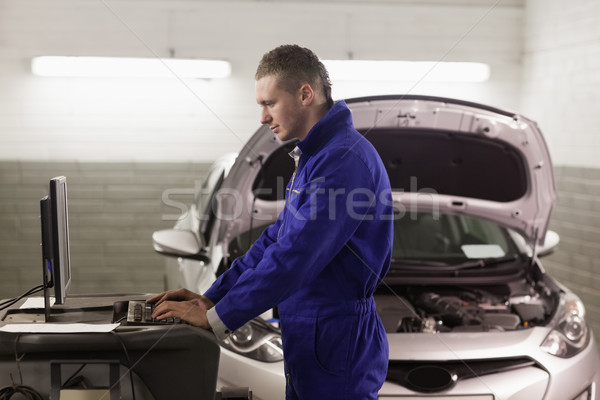 Mechanic standing while looking at a computer in a garage Stock photo © wavebreak_media