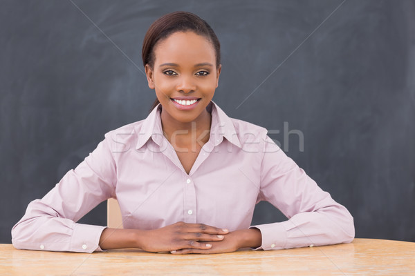 Teacher smiling while putting her hands on desk in classroom Stock photo © wavebreak_media