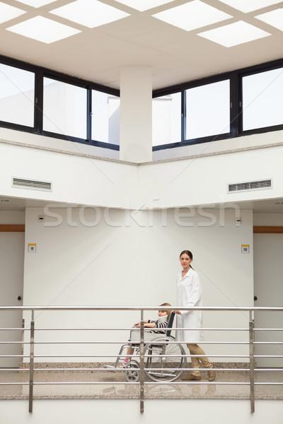 Médico empujando nino cuello silla de ruedas hospital Foto stock © wavebreak_media